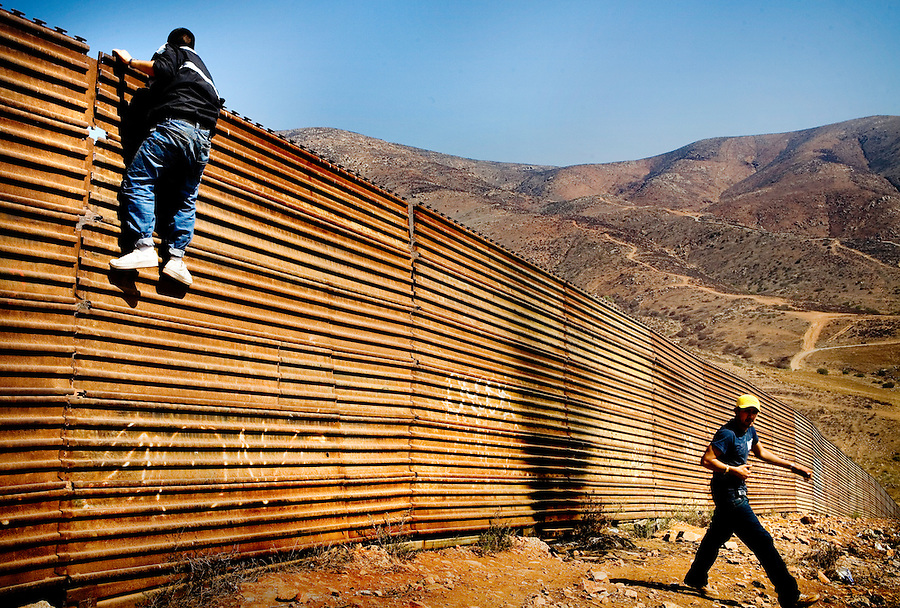 Tijuana, Baja California, MX, Oct. 14, 2007 - Two young men (refused to give their names) watch for the the U.S. Border Patrol as they try to cross in the Otay section of Tijuana. The two said they were crossing to find jobs to help support their families. The U.S. Border Patrol says that this area is one of the more popular crossings in the area.