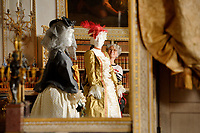"""BNPS.co.uk (01202 558833)<br /> Pic: ZacharyCulpin/BNPS<br /> <br /> Denise is reflected in one of the grand mirror's at  Uppark as she applies the finishing touches to the spectacular paper costumes. <br /> <br /> Ori-garments -  Artist Denise Watson has created a stunning 1750's masquerade Christmas Ball with characters made entirely from paper at the National Trust's Uppark House in West Sussex.<br /> <br /> Denise has dressed 14 shop mannequins with clothes, shoes, masks, fans, floral details, hair and even jewellery made from things like tissue paper, gift wrap and brown parcel paper. <br /> <br /> The festive display was inspired by Admiral Lord Gambier's memoirs in which he quotes from Lady Sarah Featherstonhaugh's journal of 1753 where she wrote: """" The whole party afterwards proceed to Uppark, where they passed a cheerful happy Christmas in the most friendly society, and enlivened their neighbourhood with some masked balls.""""<br />  <br /> The design to the finished result took a total of three months. Denise said, """"I am really delighted with the final result. It has been a joy to work at Uppark using the grand rooms and to recreate an event which actually took place""""."""