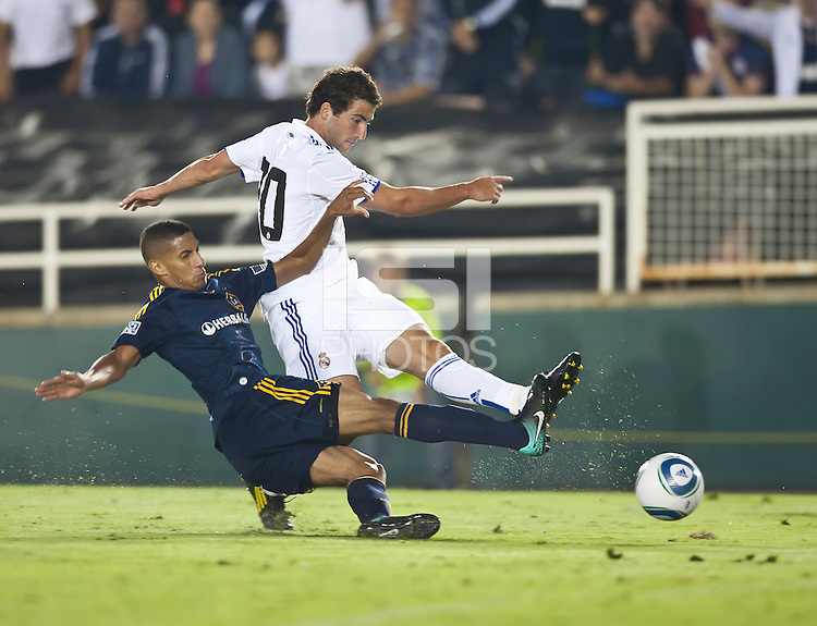 Real forward Gonzalo Higuain (20) holds off Galaxy defender Sean Franklin (28) during the second half of the friendly game between LA Galaxy and Real Madrid at the Rose Bowl in Pasadena, CA, on August 7, 2010. LA Galaxy 2, Real Madrid 3.