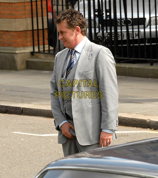 "SHANE RICHIE.On the set of ""Minder"", Lincoln Inn Fields, Holborn, London, England..Shane Richie will star as Archie Daley, the nephew of Arthur Daley, played by George Cole between 1979-1994..August 16th, 2008.filming acting grey gray suit waistcoat grabbing crotch profile half length gesture funny  .CAP/IA.©Ian Allis/Capital Pictures."