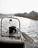 CHINA, Hangzhou, man paddles his boat on West Lake (B&W)