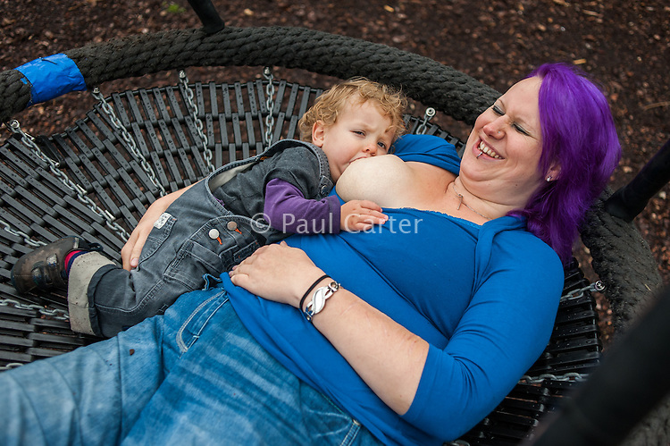 A young woman breastfeeds her toddler whist lying in a basket swing in a children's play park.<br /> <br /> 27/09/12<br /> Berkshire, England, UK