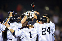 Empire State Yankees outfielder Melky Mesa is mobbed by teammates, including Austin Romine #24 and Corban Joseph #1, at home after hitting a two run walk off home run during game three of a best of five playoff series against the Pawtucket Red Sox at Frontier Field on September 7, 2012 in Rochester, New York.  Empire State defeated Pawtucket 4-3 to send the series to game four as Pawtucket leads two games to one.  (Mike Janes/Four Seam Images)