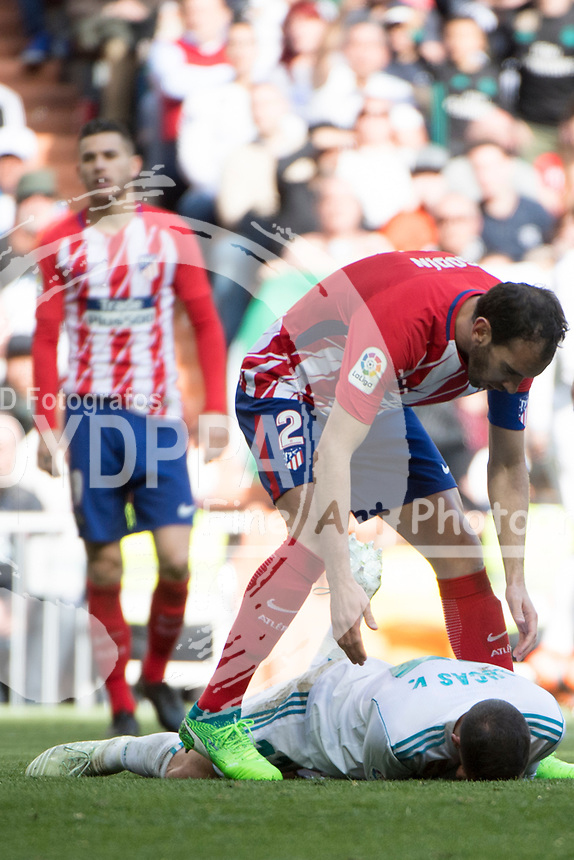 Real Madrid's Spanish midfielder Lucas Vazquez; Atletico Madrid's Uruguayan defender Diego Godin<br /> Spanish league football match Real Madrid vs Atletico de Madrid at the Santiago Bernabeu stadium in Madrid on April 8, 2018.