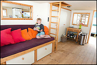 BNPS.co.uk (01202 558833)<br /> Pic: LauraDale/BNPS<br /> <br /> Cam McGregor, whose parents own the beach hut, sits and enjoys a book in the comfortable and spacious interior.<br /> <br /> A modest beach hut with no bathroom or mains electricity has gone on the market for a whopping 270,000 pounds - making it the most expensive in Britain.<br /> <br /> The asking price for the tiny wooden shack on Mudeford Spit near Christchurch, Dorset, is the same cost as a plush three-bedroom house in some parts of the country and is as much as a top-of-the-range Ferrari car.<br /> <br /> The 18ft by 12ft hut can sleep up to 12 people - four people on a mezzanine deck, four on two sofa beds and another two on a pull-out bed.<br /> <br /> The huge asking price is because it is just a stones throw away from the water boasting stunning sea views out towards the Isle of Wight and the Needles.<br /> <br /> The current owners are selling the beach hut so that they can move to another one on the same sandy strip with a different view.