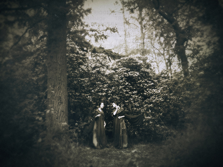 A dreamy image of two women standing among trees in a vintage wood.