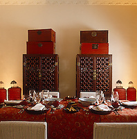 Chinese lacquered chests are piled on top of a pair of rosewood latticework cabinets in the dining room