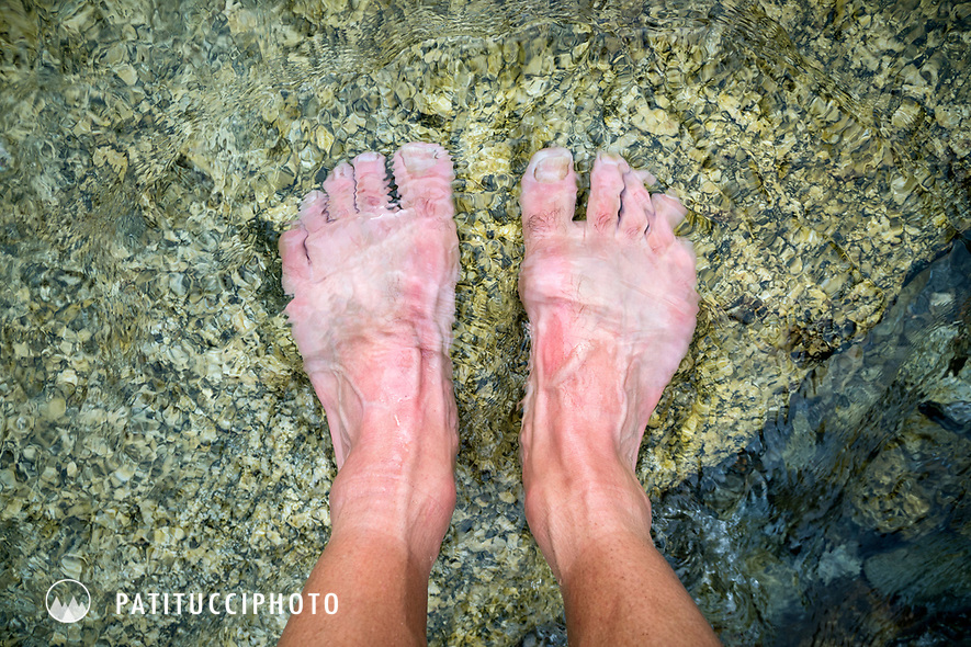 Bare feet in creek water, a trail runner takes a break while running in the Salbit area of Switzerland.