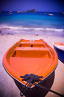 An colorful orange row boat on a Caribbean beach in front of the turqoise Caribbean Sea.