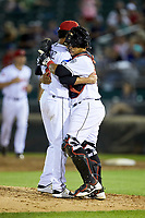 Lansing Lugnuts relief pitcher Emerson Jimenez (26) gets a hug from catcher Andres Sotillo (16) after closing out the win over the South Bend Cubs at Cooley Law School Stadium on June 15, 2018 in Lansing, Michigan. The Lugnuts defeated the Cubs 6-4.  (Brian Westerholt/Four Seam Images)