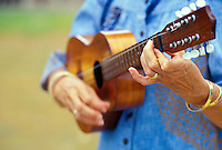 close up of a woman playing ukulele