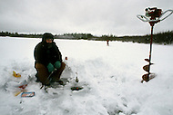 Area of North Pole, Alaska, U.S.A, January 1989. A sudden cold wave struck Alaska resulting to the temperature falling under 50 degrees Centigrade (58 degrees Fahrenheit). Leo Bettinger try to fish breaking the ice.