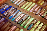 Box of pastels in an artist studio.