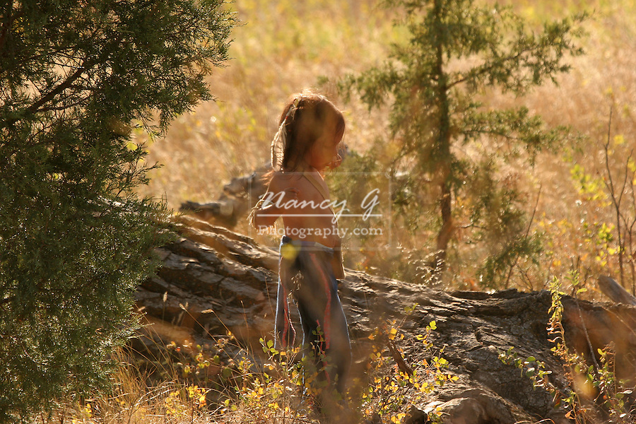 A young Native American Indian boy playing in the woods in the Fall season