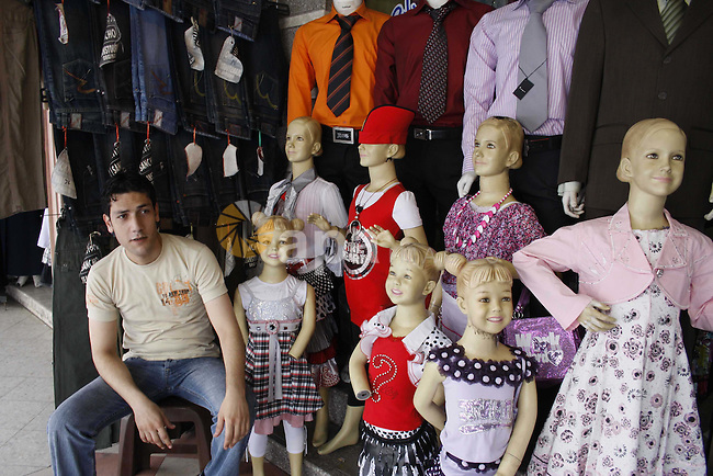 "A Palestinians buy a school uniform and bags during a preparing to the new school year at a popular market ""El-Saha"" central Gaza City on Aug 12, 2009. Photo By Ashraf Amra"