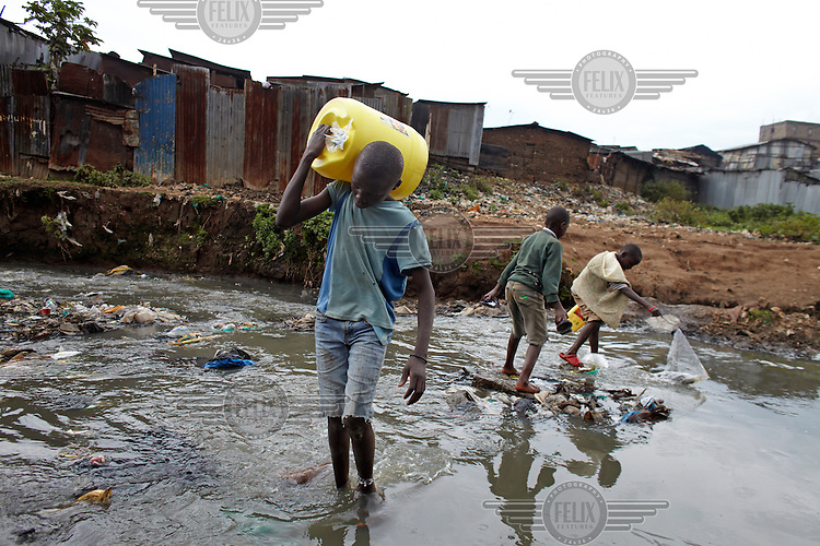 A boy carries a water container across a polluted stream in the Mathare slum. This district is home to half a million people the majority of whom live in extreme poverty.