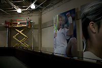 Flushing, NY - 18 August 2005 - Workers install giant posters inside the Arthur Ash court at the National Tennis Center in Flushing, Queens, NY, USA, during preparations for the 2005 US Open, 18 August 2005.
