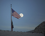 Moon rising above the American Flag.