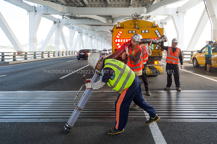9/4/2013--Busan, South Korea<br /> <br /> Workers remove dirt from expansion joints on the Gwangan Bridge in Busan (Pusan).<br /> <br /> Photograph by Stuart Isett<br /> &copy;2013 Stuart Isett. All rights reserved.