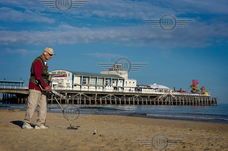 A man sweeps his metal detector over the beach near the pier in Bournemouth, Dorset.