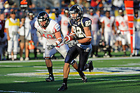 27 November 2010:  FIU wide receiver Greg Ellingson (82) takes a reception for extra yards with Arkansas State linebacker Nathan Herrold (40) in pursuit in the second quarter as the FIU Golden Panthers defeated the Arkansas State Red Wolves, 31-24, at FIU Stadium in Miami, Florida.