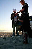 San Diego Police officer Mark Soulia and his partner officer Larry Hesselgesser cite Clayton Morgan for drinking on Mission Beach, Friday evening February 15 2008.  Hesselgesser said that it was the first day that they were actually citing offenders for drinking on the beach instead of just warning them.  Soulia said that it was the second citation that they had issued that day.  Clayton said that he was unaware of the change in the law and was about to light a cigarette when he was informed by Hesselgeser that smoking has also been banned on the beach.