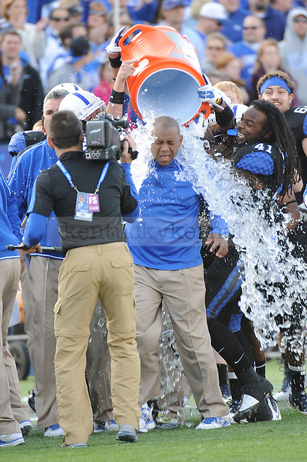 UK Head Coach Joker Phillips is given a bath to celebrate the win over Tennessee for the first time since 1984 during the second half of the University of Kentucky football game against Tennessee at Commonwealth Stadium in Lexington, Ky., on 11/26/11. UK won the game 10-7. Photo by Bob Weaver | Staff