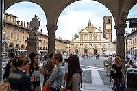 Vigevano (Pavia), piazza Ducale. Ragazze conversano sotto ai portici. In fondo il Duomo, la cattedrale di Sant'Ambrogio, e la statua di San Giovanni Nepomuceno --- Vigevano (Pavia), Ducale square. Girls talking under the arcades. On the background the cathedral of St. Ambrose and the statue of John of Nepomuk