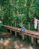 PERU, Amazon Rainforest, South America, Latin America, kids fishing at Tambopata river with mother standing on bridge