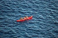 Red canoe being paddled in the Atlantic of La Gomera coast. La Gomera, Canary Islands.