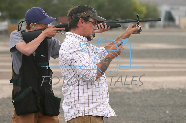 Carson City Visitors Bureau Social Media Coordinator Kyle Horvath adjusts a GoPro attached to Grant Swift's barrell at the Capital City Gun Club, in Carson City, Nev., on Friday, July 11, 2014.<br /> Photo by Cathleen Allison