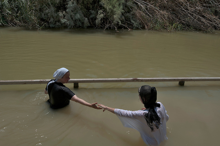 Christian pilgrims enter the Jordan River, at the baptism site of Qasr el-Yahud, near Jericho, Jordan Valley, West Bank. The site is traditionally believed to be the place where Jesus was baptized.