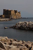 Napoli: A beautiful view from the coast of the Ovo castle (the castle of the Egg), enlightened by the sun. It is located on a little isle in a central position on the town's seafront, that is connected to the mainland by a short passage. Digitally Improved Photo.