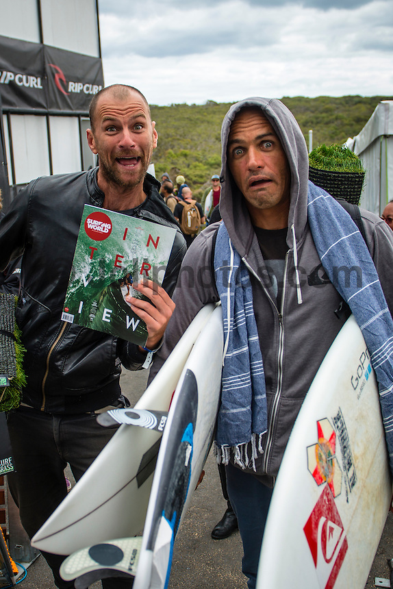 BELLS BEACH, Victoria/AUS (Friday, March 29, 2013) Surfing World editor Adam Blakey (AUS) showing Kelly Slater (USA) his latest cover of the magazine.. - The ASP Top 34 returned to battle today as the Rip Curl Pro Bells Beach presented by Ford completed Round 1 of competition in clean three-to-four foot (1 metre) waves at Bells Beach..Stop No. 2 of 10 on the 2013 ASP World Championship Tour (WCT), the Rip Curl Pro Bells Beach recommences the hunt for this year's world surfing crown and the perennial threats were in blistering form on opening day..Kelly Slater (USA), 41, 11-time ASP World Champion, posted an emphatic victory over a lethal Adam Melling (AUS), 28, and wildcard Jacob Willcox (AUS), 15, in Round 1 of competition this afternoon. Slater's commanding display at Rincon point netted him the day's high heat total of an 18.07 out of a possible 20, including a near-perfect 9.70 on his final wave of the heat...Following a Runner-Up finish in 2012, Slater is back with a vengeance this season, collecting a win at the opening event on the Gold Coast and announcing his intentions for the year ahead..Joel Parkinson (AUS), 31, reigning ASP World Champion, has collected three Rip Curl Pro Bells Beach victories (2004, 2009, 2011) throughout his storied career and the stylish natural-footer continued his impressive run at the iconic break in Round 1 this morning..Parkinson was joined by Gold Coast stablemate and two-time ASP World Champion (2007, 2009) Mick Fanning (AUS), 31, today as back-to-back Round 1 victors with Fanning slicing through the morning conditions and directly into Round 3..Julian Wilson (AUS), 24, current ASP WCT No. 5, survived a hard-fought battle with Kai Otton (AUS), 33, and Patrick Gudauskas (USA), 27, to punctuate this morning's action...Long considered one of the premiere surfers on the planet, Wilson's start to the 2013 season has positioned the young Sunshine Coaster in the hunt for the 2013 ASP World Title..While the top seeds dominated the ope