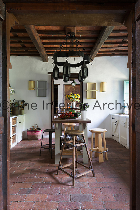 A view into the kitchen. Traditional local materials were kept during the restoration of the house, such as the terracotta tiles on the floor and ceilings and the original massive wooden beams. Arts and Crafts lanterns hang above the central table.
