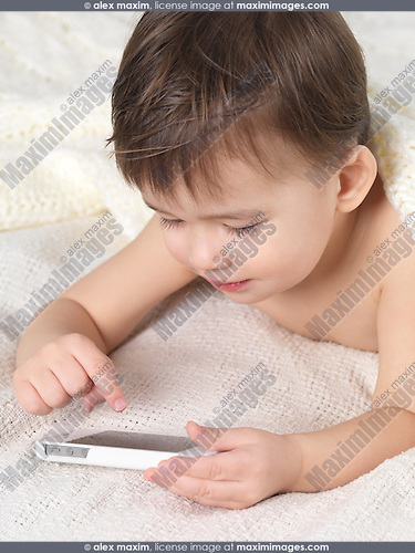 Two year old boy with an iPhone in his hands