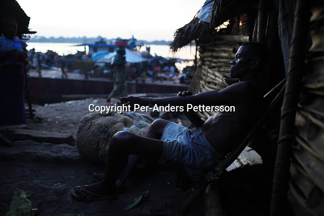 MBANDAKA, DEMOCRATIC REPUBLIC OF CONGO APRIL 14: Tabo Evariste, age 58, relaxes outside his house on April 14, 2006 in the port in Mbandaka, Congo, DRC. Mr. Evariste is a fisherman, and started fishing with his father when he was two years old. The port is a big trading point, and about 700 kilometers from the capital Kinshasa. Many villagers come here to trade goods. The Congo River is a lifeline for millions of people, who depend on it for transport and trade. Congo is planning to hold general elections by July 2006, the first democratic elections in forty years..(Photo by Per-Anders Pettersson/Getty Images)..