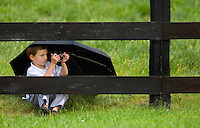 A young boy take a picture of the horses during the Queen's Cup Steeplechase in Mineral Springs, NC.
