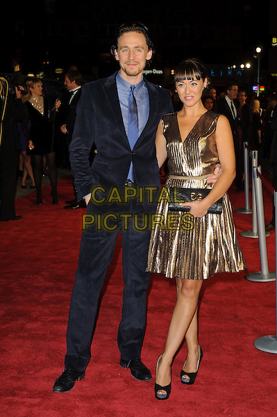 Tom Hiddleston & guest.'360' opening gala premiere, 55th BFI London Film Festival, Odeon cinema, Leicester Square, London, England..October 12th 2011.full length black blue suit shirt tie gold dress clutch bag.CAP/CJ.©Chris Joseph/Capital Pictures.