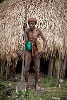Sage, about 80, wearing a 'koteka' (a gourd penis sheath) near his house in Seima village. He is the last man in Seima who lives in a traditional Dani way. However, to facilitate his daily routine, he uses plastic jerrycans to transport water from the river and a shovel (instead of wooden hoe) to cultivate his land.