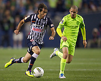 CF Monterrey forward César Delgado dribbles the ball past Seattle Sounders FC midfielder Osvaldo Alonso during a CONCACAF Champions League match between the Seattle Sounders FC and CF Monterrey at CenturyLink Field in Seattle Tuesday Oct. 18, 2011. CF Monterrey won the game 2-1.