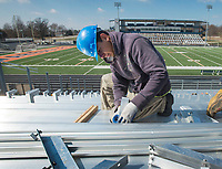 NWA Democrat-Gazette/BEN GOFF @NWABENGOFF<br /> Gustavo Armendariz with a crew from Southern Trades, Inc. out of Louisville, Ky., install new bleachers Thursday, March 1, 2018, in Gates Stadium at Rogers Heritage High. The stadium is getting all new aluminum bleachers on both the home and visitor sides, as well as a new walkway on the front of the home side.