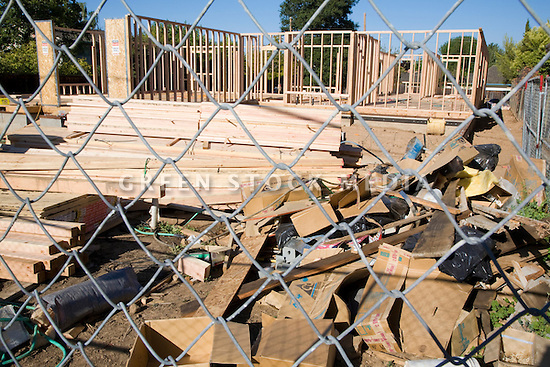 A wooden house frame viewed through a fence. The house is being built in conventional building methods which consumes a large amount of natural resources such as trees used for lumber. Cupertino, California, USA