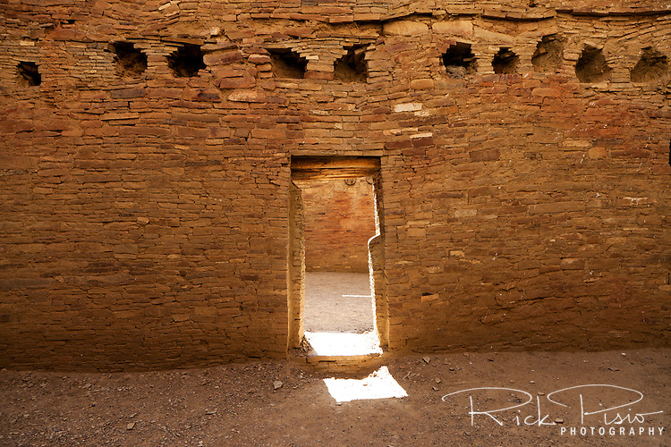 Light shines through a doorway within Pueblo Bonito at Chaco Culture National Historical Park in New Mexico.