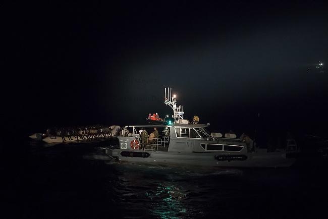 Die Sea Watch-2 Crew war am Freitag den 21. Oktober 2016 in den fruehen Morgenstunden waehrend ihrer 13. SAR-Mission vor der libyschen Kueste zu einer Position ausserhalb der 12 Meilenzone gerufen worden. Es war ein Fluechtlingsschlauchboot gesichtet worden. Als die Sea Watch-2 dort eintraf sah sie ca. 150 Menschen zusammengepfercht in einem ueberfuellten Schlauchboot sitzen. Eine Versorgung der Menschen auf dem Fluechtlingsschlauchboot mit Rettungswesten durch die Rettungs Boote der Sea Watch-2 wurde von der libyschen Kuestenwache unterbunden. Ein Soldat der Kuestenwache enterte das Schlauchboot vom Bug und machte sich dann an dem Aussenbordmotor zu schaffen. Auf dem Weg dahin schlug und trat er die Gefluechteten ein. Nach einigen Minuten entfernte sich das Boot der Kuestenwache. Dann verlor der Bug des Schlauchbootes seine Luft und es brach Panik bei den Gefluechteten aus. Sie sprangen in das Wasser und versuchten zum Schiff Sea Watch-2 zu gelangen. Die Crew warf ihnen Schwimmwesten und Rettungsringe zu, die Besatzungen der Rettungsboote der Sea Watch-2 zogen Menschen aus dem Meer, dennoch sind bis zu 30 Menschen ertrunken. Vier Ertrunkene konnten von der Sea Watch geborgen werden.<br /> Im Bild: Die Libysche Kuestenwache (rechts), das Fluechtlingsboot und ein Rettungsboot der Sea Watch-2 mit Schwimmwesten.<br /> 21.10.2016, Mediterranean Sea<br /> Copyright: Christian-Ditsch.de<br /> [Inhaltsveraendernde Manipulation des Fotos nur nach ausdruecklicher Genehmigung des Fotografen. Vereinbarungen ueber Abtretung von Persoenlichkeitsrechten/Model Release der abgebildeten Person/Personen liegen nicht vor. NO MODEL RELEASE! Nur fuer Redaktionelle Zwecke. Don't publish without copyright Christian-Ditsch.de, Veroeffentlichung nur mit Fotografennennung, sowie gegen Honorar, MwSt. und Beleg. Konto: I N G - D i B a, IBAN DE58500105175400192269, BIC INGDDEFFXXX, Kontakt: post@christian-ditsch.de<br /> Bei der Bearbeitung der Dateiinformationen darf die Urheberkennzeichnung i