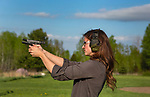 Young woman shooting a Smith & Wesson M&P Shield pistol