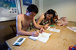 Volunteers fill in their dive log after planting coral on the seabed in the bay at Onna Village, Okinawa Prefecture, Japan, on Saturday, June 23, 2012. Photographer: Robert Gilhooly
