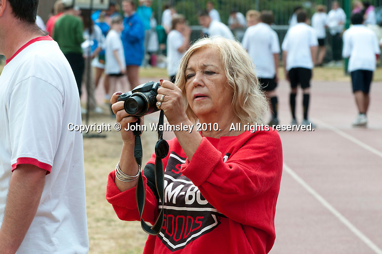 Teacher taking photos, Sports Day. state secondary school.