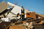 Woman on pile of rubble of house destroyed by tornado