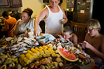 Raymond and Yvonne Landry prepare a crab boil dinner with crabs that Raymond caught earlier in the day.  ..The Landry family, relatives and friends.  Yvonne and Raymond, natives of southern Louisiana, at home and crabbing in St. Bernard's Parish.  Following the BP Oil Spill, the family has continued to fish for crab, navigating through daily closures and openings to find crab grounds that haven't been impacted by the spill.  Fishing restrictions have prevented them from following the annual movement of the crab up and down the bayou, sometimes leaving them high and dry when the crab migrate into closed areas.